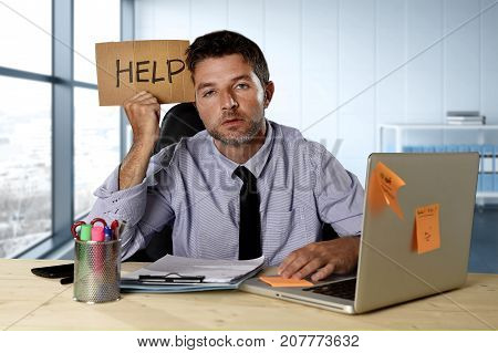young desperate businessman suffering stress working at computer desk holding sign asking for help looking tired exhausted and overwhelmed by heavy work load at modern office workplace