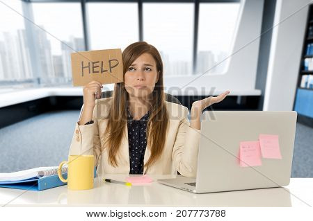 young attractive sad and desperate business woman suffering stress at office laptop computer desk holding help sign looking depressed and overwhelmed in business crisis and problem concept