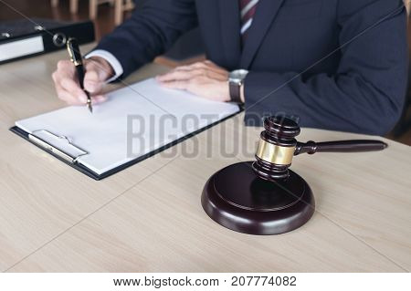 Close up of gavel and Report the case with Male Judge note paper on wooden table in courtroom Law and justice concept.