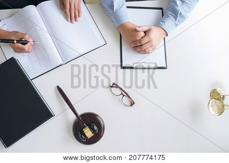 Close up of gavel Male lawyer or judge Consult with client and working with Law book report the case on table in modern office Law and justice concept. Top view.
