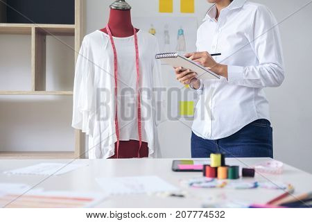Stylish fashion designer working with measure red dummy as sketches in Draft book of new collection in art profession and job occupation Creative Design and Artistic Concept.