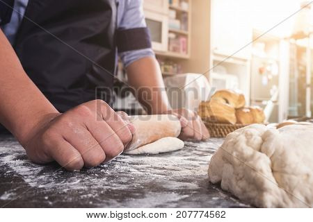 Male hands kneading dough sprinkled with flour table Hands preparing bread Raw dough for bread with ingredients on black background.