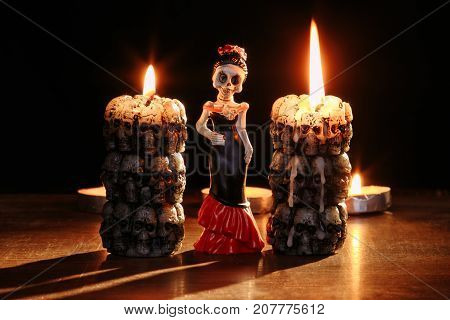 figures of single skeletons of the woman against the background of the burning candles in the form of skeletons