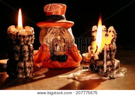 in a candlestick in the form of the skeleton dressed in a dress coat and a hat the candle burns.