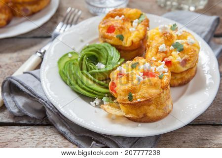 Delicious egg muffins with ham, cheese, avocado, feta and vegetables