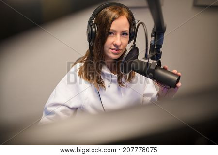 Young confident female jockey using headphones and microphone in radio studio