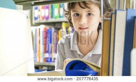 smiley white boy with the book and the bookshelf at background