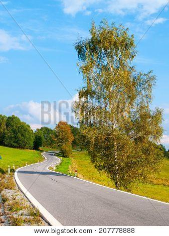 Winding asphalt road in rural landscape of Sumava Mountains, Czech Republic.