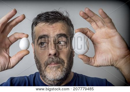 Man compares ironically two eggs one of smaller size, isolated on white background