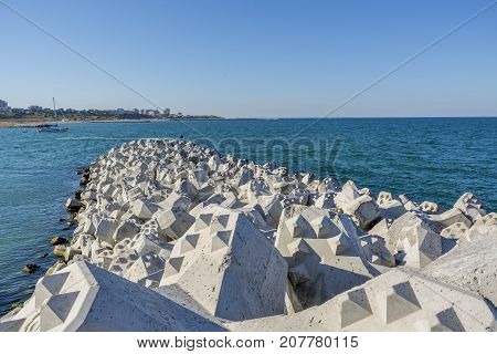 Tetra-pods or concrete breakwater blocks at Tomis, Constanta harbour. Sea wall for protect the beach. Breakwaters concrete tetra-pods.