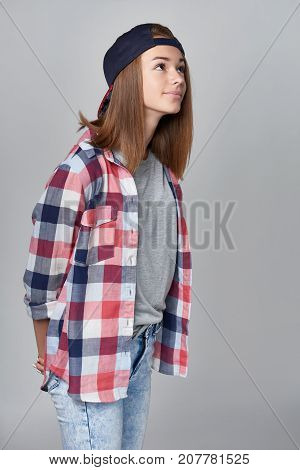 Teen girl in casual clothing looking peering up at blank copy space, isolated on grey background