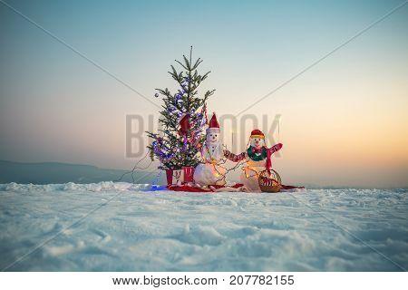 Snowmen Celebrate Christmas Near Christmas Tree. Snow In The Mountains. Two Snowmen On The Snow. Chr