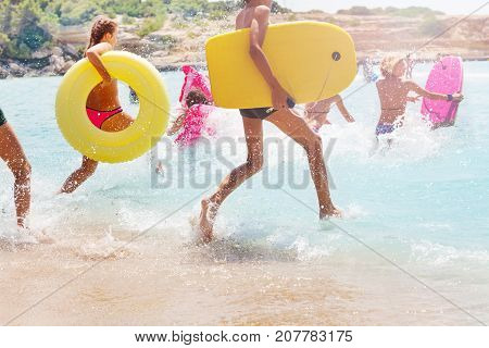 Group of many kids running into the sea water with equipment board inflated swim rings making splashes