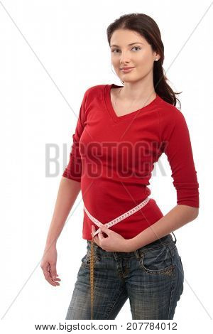Teenage girl measuring her slim waist with measuring tape, looking at camera, smiling. Isolated on white.