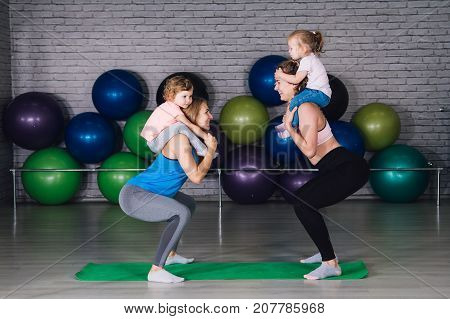 Two Young Sports Mom And Baby Girls Do Exercises Together In The