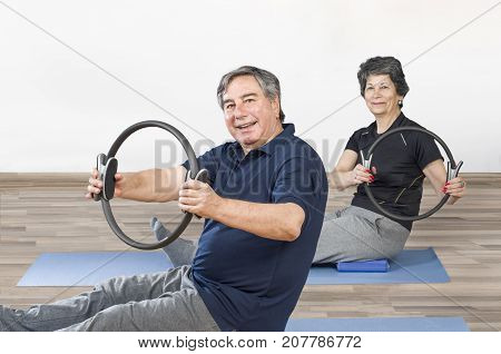 Two Senior People In A Gym Class Lying On Mats Doing Pilates Exercise With Ring