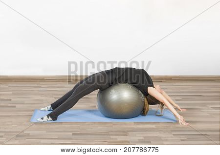Woman in a gym class on a mat doing Pilates exercise with ball pilates. Stretching.