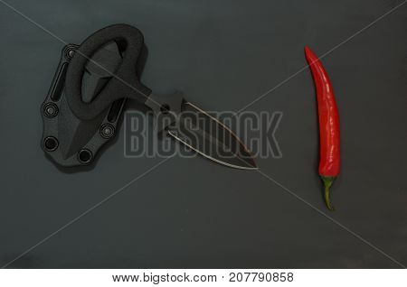 Sharp Knife And Chili Pepper. Diagonal Composition. Black And Red.