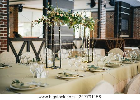 In the middle of the table is a composition of flowers and garland on a metal stand. decoration of the table for a festive dinner in warm evening color.