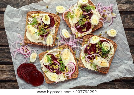Danish open-face rye sandwich with quail eggs, beetroot, pickled onions and cucumbers drizzled with dill. poster
