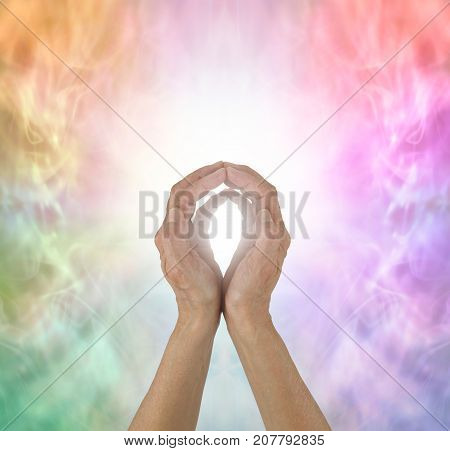 Rainbow Spectrum Energy healing hands - female  hands with fingertips touching on a wispy ethereal rainbow coloured background and a ball of white light plus copy space all around