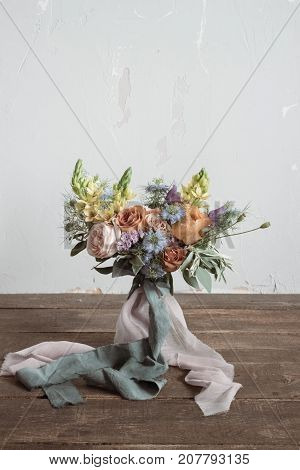 Analog film styled photo of beautiful wedding bouquet of roses in pastel shades with ligt pink and grey tapes