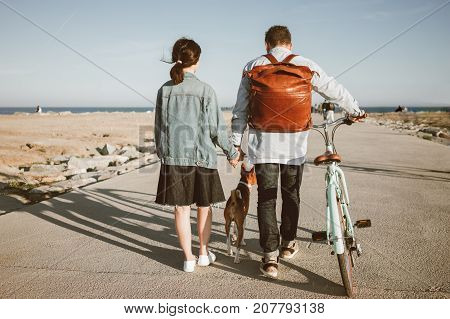 Girl in denim dress and jacket with man in jeans and blue shirt with leather brown backpack. Couple walks to sea on beach with basenji dog and holds hands guy leads girlfriend's mint bike. Overall view from back.