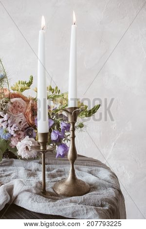 Analog film styled photo of beautiful wedding bouquet of roses in pastel shades with candles in vintage candlesticks in front view