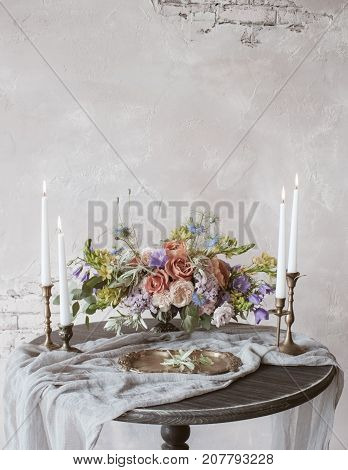 Analog film styled photo of beautiful wedding composition of roses in pastel shades with candles in vintage candlesticks on wooden table