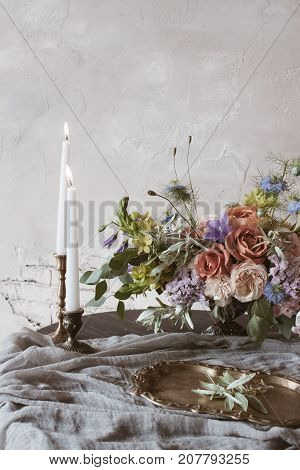 Analog film styled photo of beautiful wedding composition of roses in pastel shades with candles in vintage candlesticks on wooden table with handcrafted textile