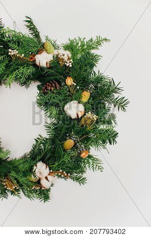 Half of christmas handmade wreath with coniferous branches cotton flowers silver brunia and leucadendron on white wall