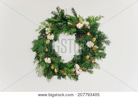Christmas handmade wreath with coniferous branches cotton flowers silver brunia and leucadendron on white wall