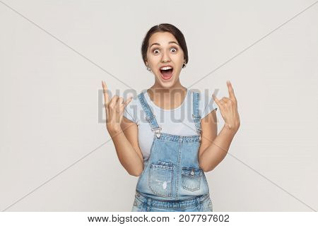 Rock N Roll. Funny Spanish Woman In Denim Overalls, Looking At Camera With Rock Sing.