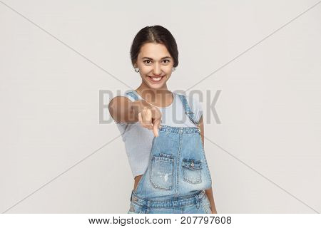 Hey You! Young Adult Woman, Pointing Finger And Looking At Camera With Toothy Smile. On Gray Backgro