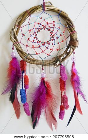 Photo of handmade dreamcatcher with feathers and beads on a white background