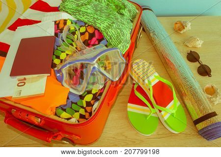 Open suitcase packed for travelling close up. Suitcase with different things prepared for travel - Retro color
