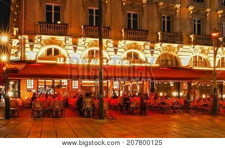 Paris, France - October 05, 2017: the traditional French cafe Le Depart Saint Michel with unidentified people at night. It located on the bank of Seine river in Paris.