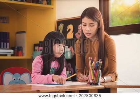 Teacher and student take home work togather in preschool Library mother art school teacher education and kid concept