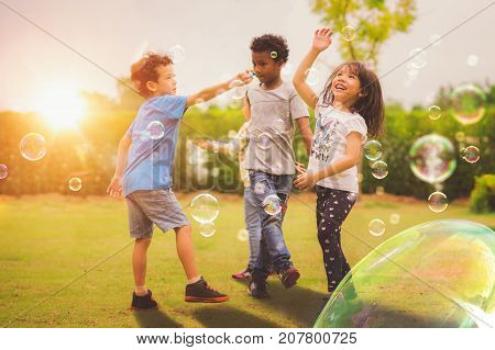 Kid and friends in international pre school play a bubble in playground with sunset background kid child school play and summer background