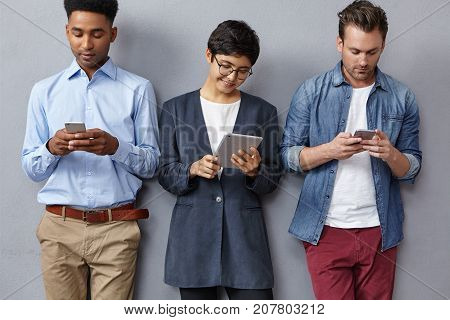 Focused Fashionable Youngsters Of Diffeent Nations, Read Attentively Information In Tablet And Smart