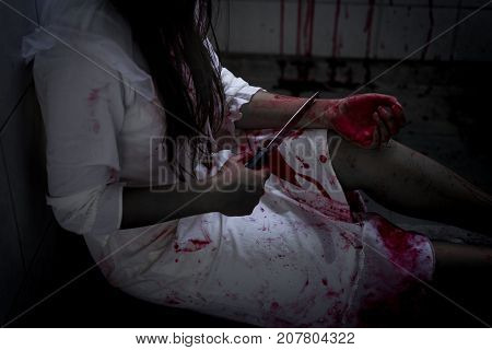Ghost woman or zombie holding knife for kill yourself with blood violence in house of ruin nightmare horror of scary fear on hell is monster devil in halloween festival.
