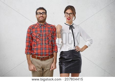 Annoyed Female Points At Male Nerd, Feels Bored And Irritated With Him. Shy Closed Man In Old Fashio