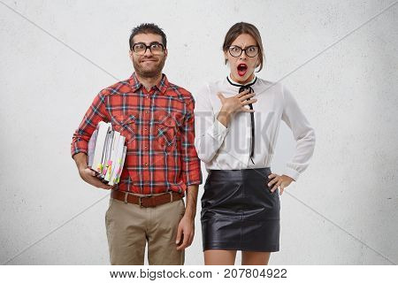 Clever Bearded Young Man With Many Books, Going To Teach Beautiful Woman Who Looks In Discontent And