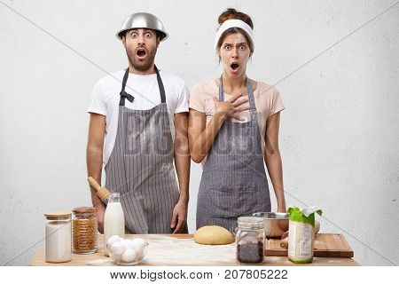 Terrifiied Female And Male Cooks Look With Widely Opened Mouth, Stand At Kitchen, Find Out That They