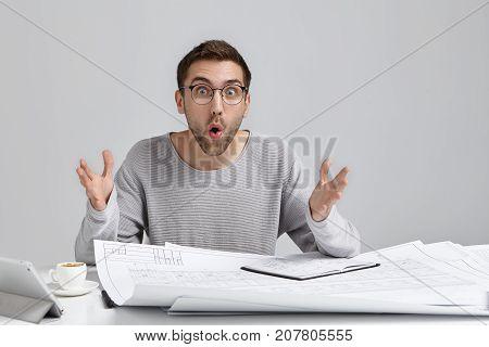 Unshaven Surprised Male Designer At Work Desk, Gestures In Shocked Expression, Looks Bugged Eyes Say