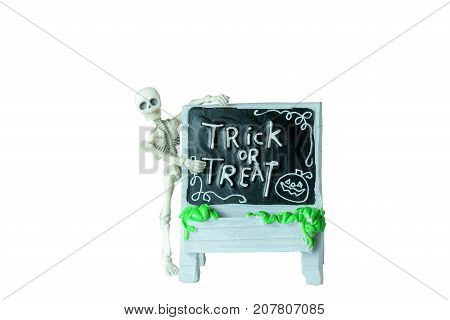 Halloween concept : Plastic human skeleton model climbing on dirty ceramic Trick or Treat sign isolated on white background
