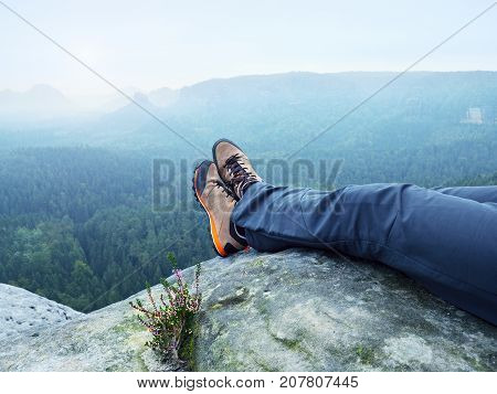 Tired Man Hiker Lay Down And Enjoy View Into Landscape Over His Tired Legs In Tourist Boots