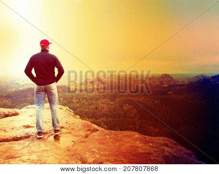 Hiker Man Stays On A Rocky Ridge And Enjoy View Over Long Valley To Horizon. Cold Sun Hidden In Clou