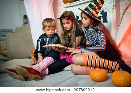 Group of cute kids wearing Halloween costumes gathered together at living room decorated for holiday and reading short scary stories