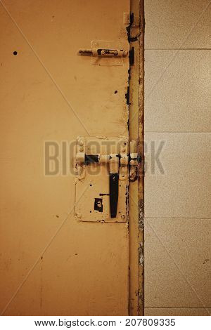 Close up view of yellow metallic door with bolt lock in old prison.